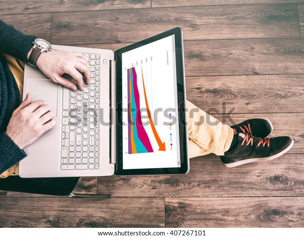 Man working at computer laptop with the finance report on the screen. Business Research, Economy Statistics