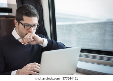 man working with computer on a train