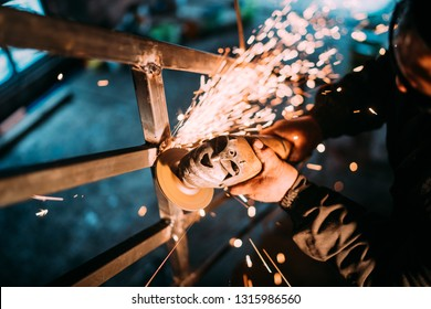man working in construction industry and cutting metal with disc angle grinder