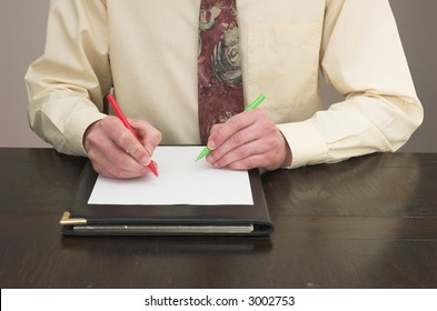 Man working at desk with pens in both hands!