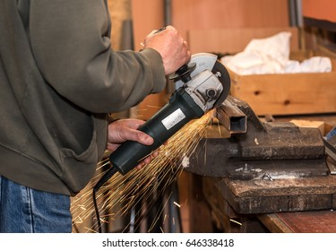 Man working with electric grinder tool on steel structure in workshop