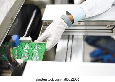 Man working in an electronics factory removing printing circuit board from SMT line. Image taken at Electronics manufacturing plant and the PCB board assembled with electronic components.