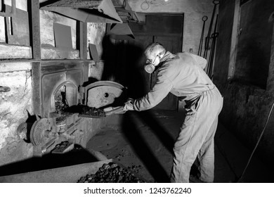 man working the furnace fueling the boiler with coal