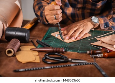 The man working with genuine leather in workshop.