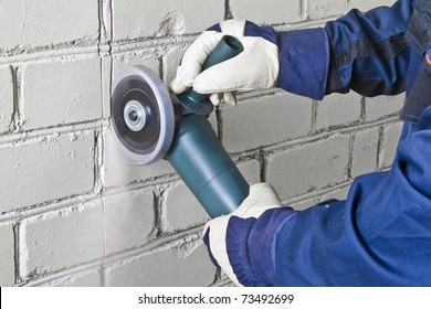 A man working with grinder, close up on tool, hands and sparks, real situation picture