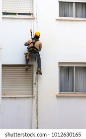 Man working at height. Building repairing. Ropes and harness. Cracks on the building.