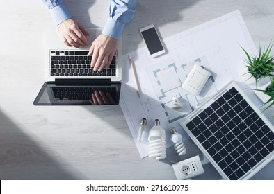 Man working at his desk on a laptop with energy saving CFL lamps, a solar panel and a house project, top view