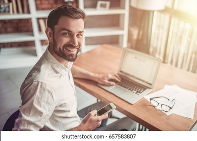 Man working with his laptop in cafe, taking smartphone in hand, smiling and looking at the camera.