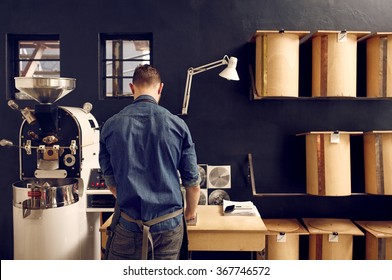 Man working in his modern coffee roastery with neat storage