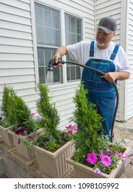 Man working in his yard surrounding his house watering potted petunias and new orborvitaes on his patio using a spray nozzle on a hosepipe