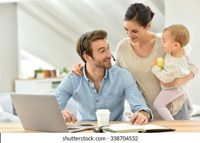 Man working from home, family around