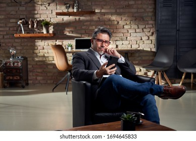 Man working in home office using phone the browse the internet.