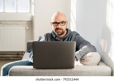 Man working at home on a laptop while relaxing on a sofa balancing it on the arm of the furniture as he works