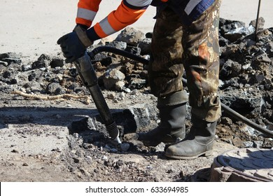 man working a jackhammer on a city street.
