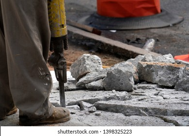 Man working with jackhammer on the road detail