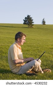 Man working with laptop in a meadow at sunset