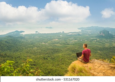 Man working with laptop sitting on the rocky mountain on beautiful scenic clif background.  Freelance concept.