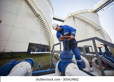 man working with large white fuel containers against blue sky