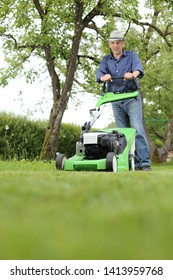 A Man working with a lawn mower in his garden
