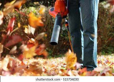 Man die werkt met bladblazer: de bladeren worden op en neer gewerveld op een zonnige dag