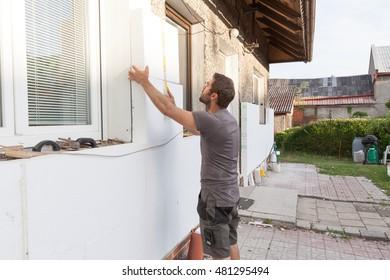 Mann arbeitet mit Zähler bei der Wärmedämmung der Fassade.