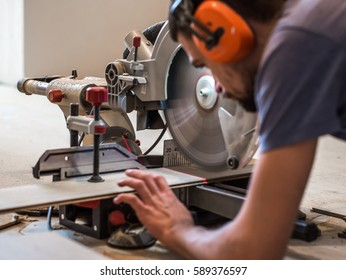 a man working with a miter saw closeup, concept building and repair