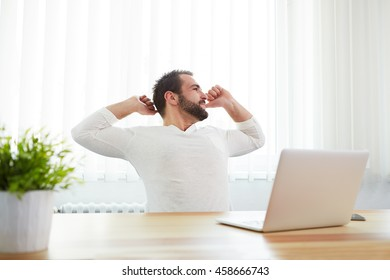 Man working in office stretching his back at desk