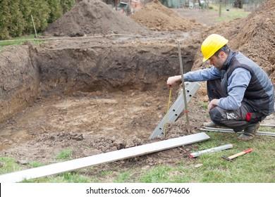 Mann, der am Bau eines Hauses mit einem privaten Pool arbeitet.