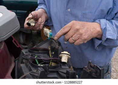 Man working on car light in junk yard