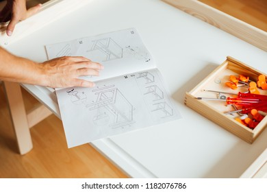 Man Working On Carpentry At Home Using Blueprint