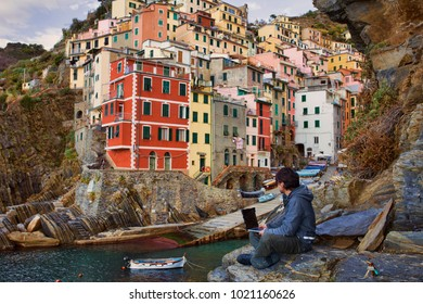 A man working on computer, laptop, sitting by the beach in the beautiful Italian coastal village, as a symbol of digital nomad lifestyle, freedom and traveling around the world