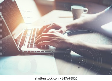 Man working on computer. Loft office, researching new business strategy. Typing new letter for big company. Intentional sun glare effect, graph and stats overlay