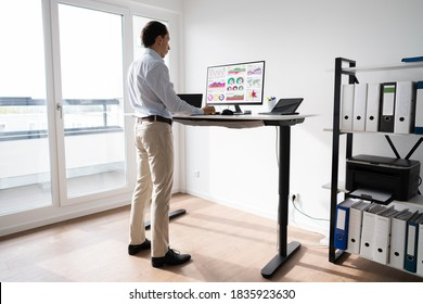 Man Working On Computer At Standing Desk In Home Office