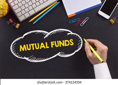 Man working on desk and writing MUTUAL FUNDS