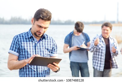 Man is working on a digital tablet. Employee team of an environ mentalist on the background of a working group of men. Ecologists are studying the pollution of the reservoir.