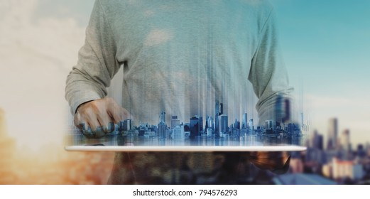 a man working on digital tablet, with Hologram futuristic modern buildings. City sunrise background