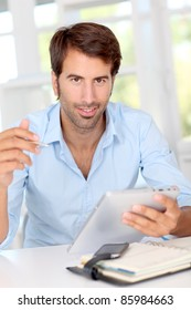 Man working on electronic tablet in office