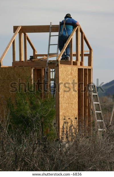 man working on frame of a building