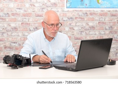 a man working on his graphics tablet and laptop