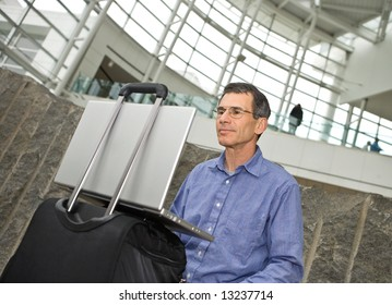 Man working on his laptop computer in Seattle airport terminal, laptop propped on his suitcase
