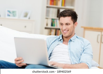 Man working on his laptop at home as he relaxes on a comfortable sofa smiling as he reads the screen