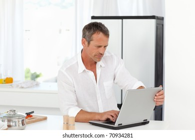 Man working on his laptop in his kitchen