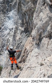 Man working on the installation of a rockfall protection mesh