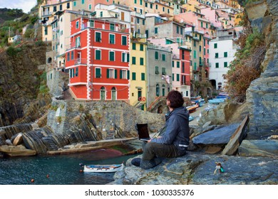 A man working on laptop, computer, by the beach in the beautiful Italian village, as a symbol of digital nomad lifestyle, early retirement, financial freedom, traveling around the world and tech work