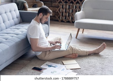 Man working on laptop computer sitting on the floor with his diary and official papers at home