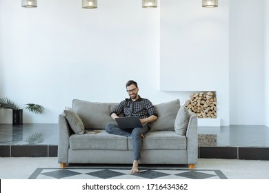 Man working on a laptop with crossed legs. Large bright living room. Working from home