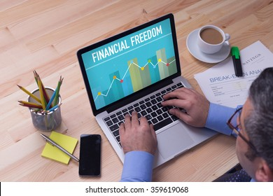 Man working on laptop with FINANCIAL FREEDOM on a screen