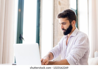 Man working on laptop from home. Counting financial data.
