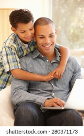 Man working on laptop at home with son