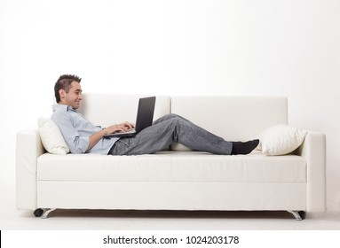man working on laptop lying on a sofa